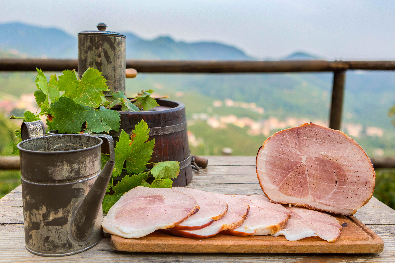Foto con visibile un prosciutto aromatizzato al miele su una tavola allestita e sullo sfondo le colline di valdobiadene