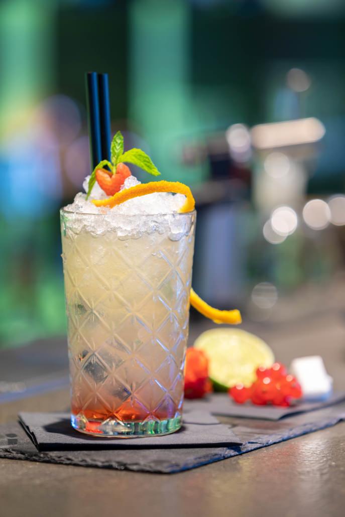 Fotografo cocktail con sfondo sfocato analcolico alla frutta sul bancone del bar