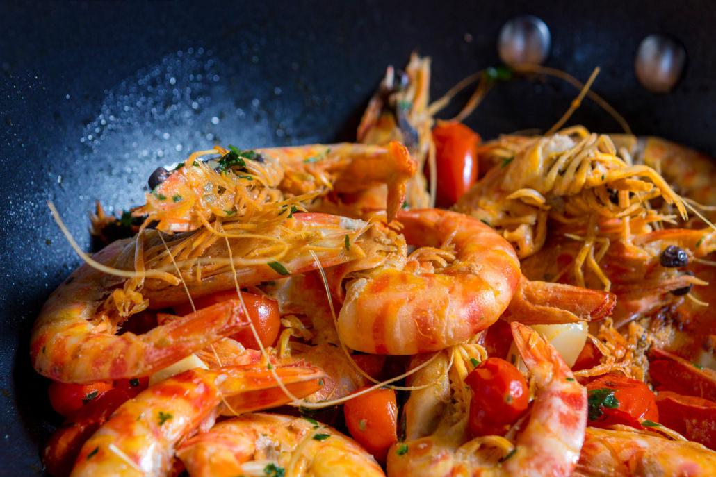 Fotografo food cucina padella di gamberi saltati in padella coi pomodori