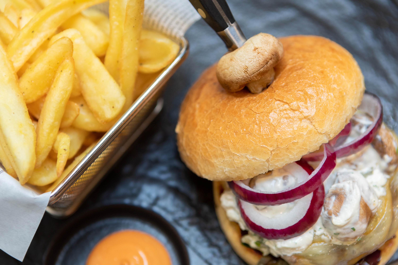 Fotografo food hamburger con cipolle su piatto nero e patatine fritte