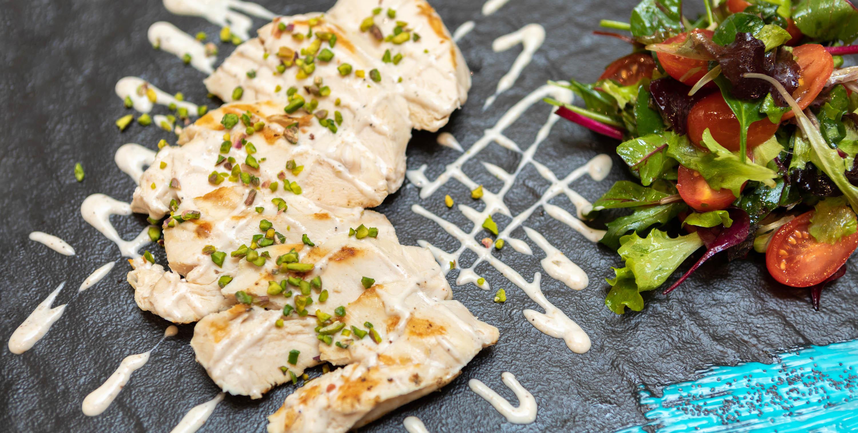 Fotografo piatti carne pollo ai ferri su piatto bianco con sala e insalata verdure coi pomodori