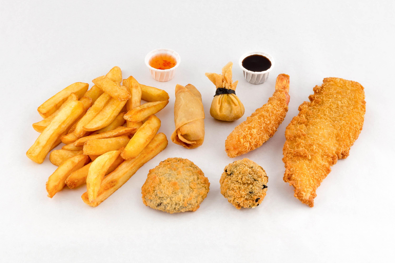 Foto di un Fritto misto con pesce, crocchette e patatine fritte su fondo bianco per pubblicità