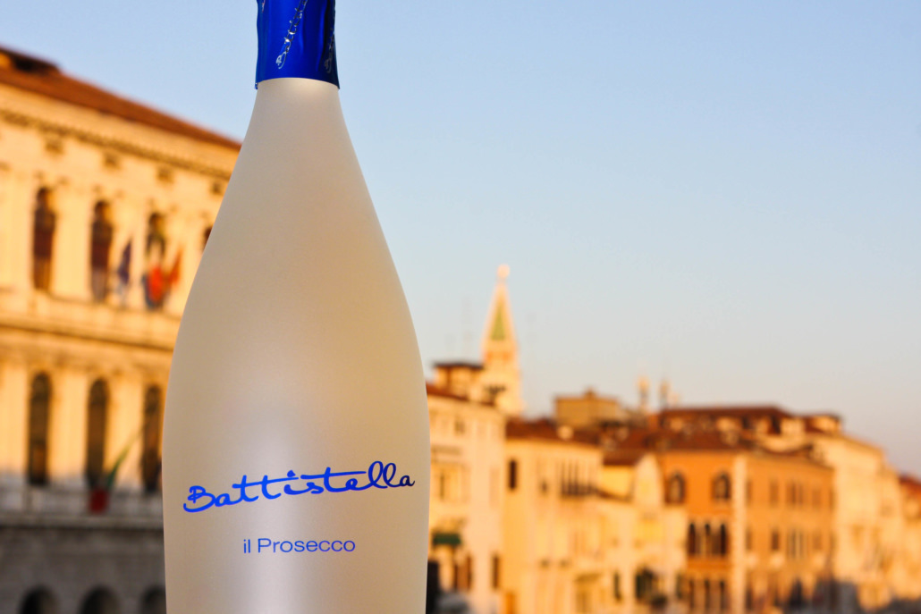 Bottiglia di prosecco con sullo sfondo una vista sfocata di venezia al tramonto