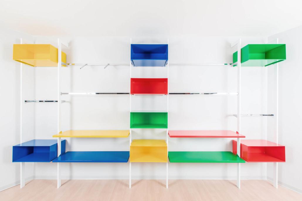 Espositore da muro con ripiani e mensole in acciaio colorate di rosso, verde, giallo e blu