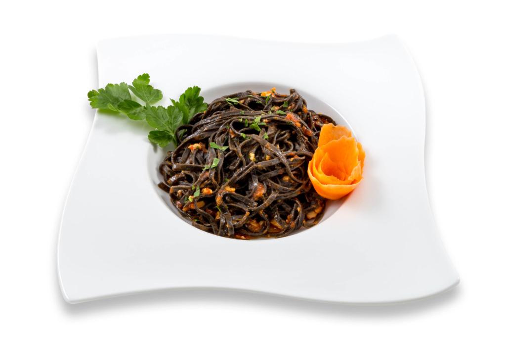 Piatto quadrato a onde su fondo bianco con spaghetti al nero di seppia